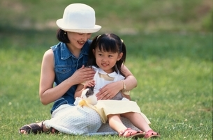 芝生に座る日本人の女の子と母親とウサギの写真素材 [FYI03167173]