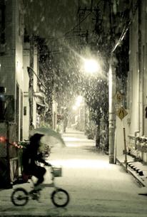 雪の中を傘をさして自転車に乗る人の写真素材 [FYI03168935]