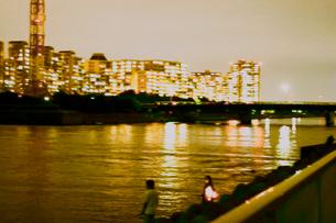 ビルの夜景と川沿いに立つ人の写真素材 [FYI03169090]
