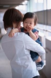 マンションの廊下で母親に抱かれる日本人の男の子の赤ちゃんの写真素材 [FYI03170322]