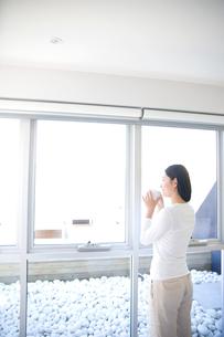 窓辺でコーヒーを飲む日本人女性の写真素材 [FYI03170425]