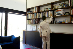 本を取ろうとする男性の写真素材 [FYI03170451]