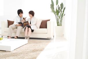 ソファで犬を抱きながら雑誌を広げる若い夫婦の写真素材 [FYI03170496]