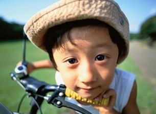 自転車と帽子をかぶって覗き込む日本人の男の子の写真素材 [FYI03171392]