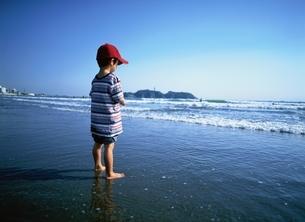 裸足で波打ち際に立つ日本人の男の子の写真素材 [FYI03171393]