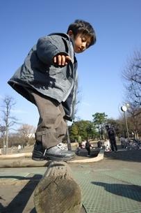 アスレチックの丸太に上る日本人の男の子の写真素材 [FYI03171413]
