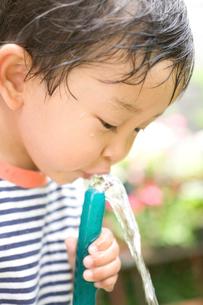 ホースで水を飲む子供の写真素材 [FYI03171481]
