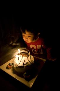 ケーキのろうそくを吹き消す男の子の写真素材 [FYI03171530]