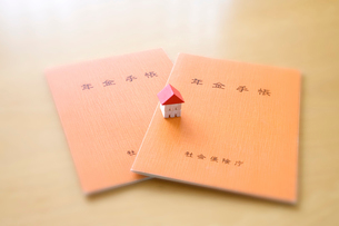 年金手帳と家のミニチュアの写真素材 [FYI03171599]