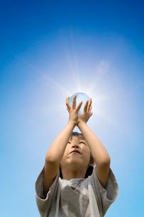 光る地球儀を掲げる男の子の写真素材 [FYI03171636]