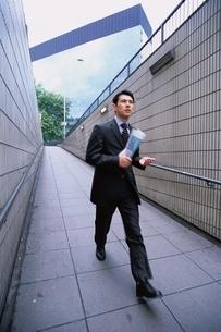 大股で通路を歩くビジネスマンの写真素材 [FYI03171833]