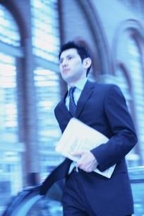書類を持ち歩くビジネスマンの写真素材 [FYI03171843]