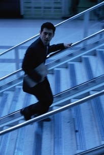 階段の手するにつかまるビジネスマンの写真素材 [FYI03171845]