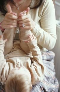 いすに座り赤ちゃんをあやす外国人の母親の写真素材 [FYI03171869]