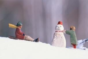 雪だるまをつくる女の子とそりをする男の子の2個の木彫りの人形の写真素材 [FYI03172019]