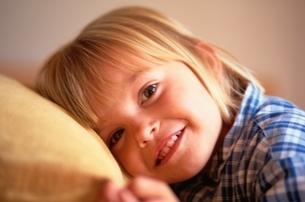 クッションに顔をあてる笑顔の外国人の女の子の写真素材 [FYI03172070]
