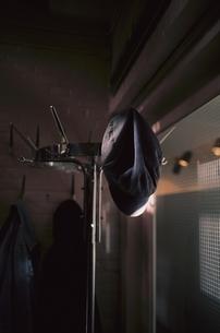 暗い室内のポールハンガーに掛かる帽子の写真素材 [FYI03172116]