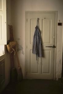 室内のドアに掛かるエプロンとほうきの写真素材 [FYI03172124]