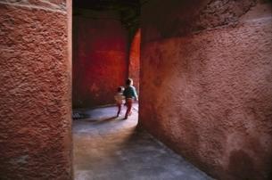 赤い壁の通路を歩く2人の子供 フランスの写真素材 [FYI03172126]
