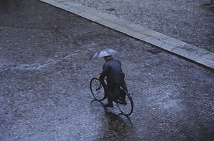傘をさし自転車に乗る男性の後姿 フランスの写真素材 [FYI03172132]