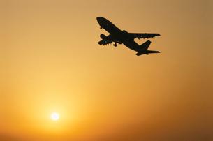 夕焼けの空を飛ぶ飛行機の写真素材 [FYI03175202]