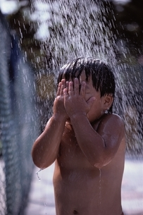 水しぶきを浴びて顔を手で覆う日本人の男の子の写真素材 [FYI03175830]