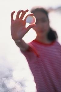 浜辺で貝殻を指にはさむ中学1年の日本人の女の子の写真素材 [FYI03175841]