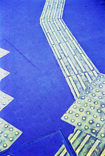 歩道に貼られた視覚障害者用の誘導施設の写真素材 [FYI03176341]