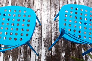 白ペンキの剥げたウッドデッキに置かれた青い椅子の写真素材 [FYI03176417]