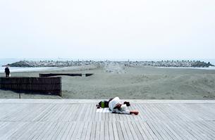 茅ヶ崎海岸のウッドデッキに横になる初老の男性の写真素材 [FYI03176439]