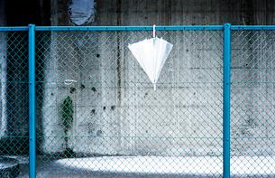 橋脚側壁の水色のフェンスにかけられたビニール傘の写真素材 [FYI03176447]
