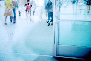 ガラスドア越しに眺めたショッピングモールの通路の写真素材 [FYI03176517]