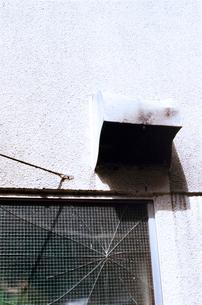 白い壁と割れたガラス窓と換気口の写真素材 [FYI03176756]