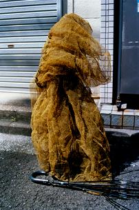 ゴミ集積場の支柱に巻かれたカラス避けの網の写真素材 [FYI03176770]