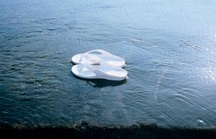 波に濡れた突堤に脱ぎ置かれた白いビーチサンダルの写真素材 [FYI03176784]