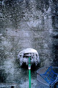 コンクリートの壁に立てかけられたモップの写真素材 [FYI03176817]
