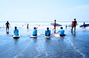 波打ち際で休息するサーファーの写真素材 [FYI03176821]