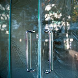 内側からビニールシートが張られている新築ビルのガラスの扉の写真素材 [FYI03176833]