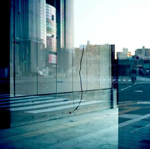 街を映す新築ビルのガラスとぶら下がった内装工事の電線の写真素材 [FYI03176837]