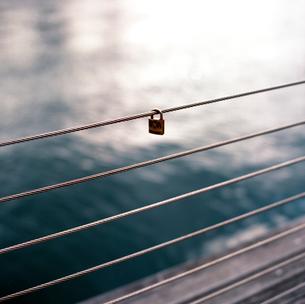 運河へのウッドデッキの柵のワイヤーに吊るされた鍵の写真素材 [FYI03176844]