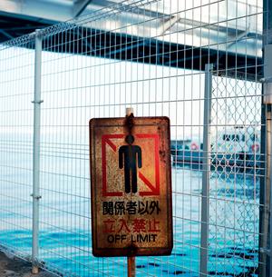 港を背にした古びた立ち入り禁止の標識の写真素材 [FYI03176847]