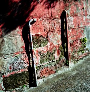 赤く塗られた古い石垣と水道管の写真素材 [FYI03176871]