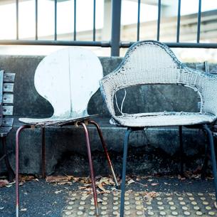 公園脇の歩道に置かれた古い椅子の写真素材 [FYI03176872]