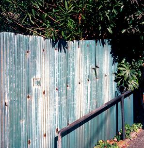 風雨にさらされたビニールトタンの塀の写真素材 [FYI03176876]