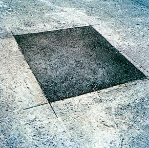 アスファルト路面の四角い補修痕の写真素材 [FYI03176899]