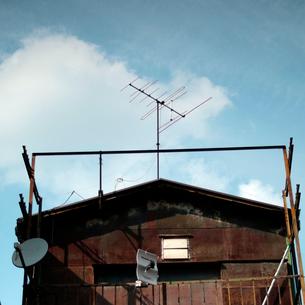 白い雲と青空を背景にした古い2階家の屋根のテレビアンテナの写真素材 [FYI03176906]