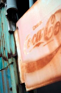 民家の軒先で剥げ落ちた飲料水の看板の写真素材 [FYI03176907]