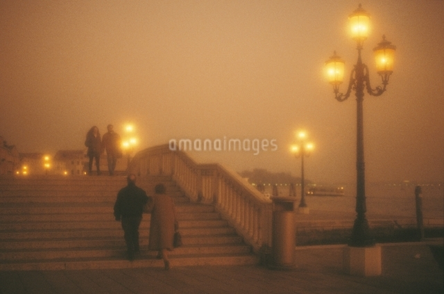 夕暮れの階段を渡る2組のカップル  ベニス イタリアの写真素材 [FYI03177305]