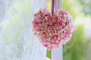 窓に掛けたハート型のバラの花束の写真素材 [FYI03177331]