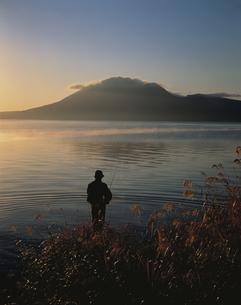 朝の支笏湖で釣りをする人のシルエット 北海道の写真素材 [FYI03177861]
